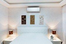 Белая кровать спальни квартиры-студии для парня